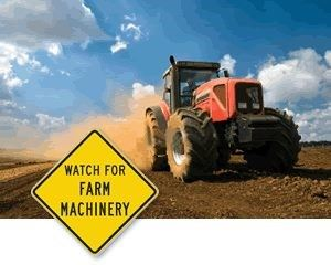 Tractor and sign that reads watch out for farm machinery