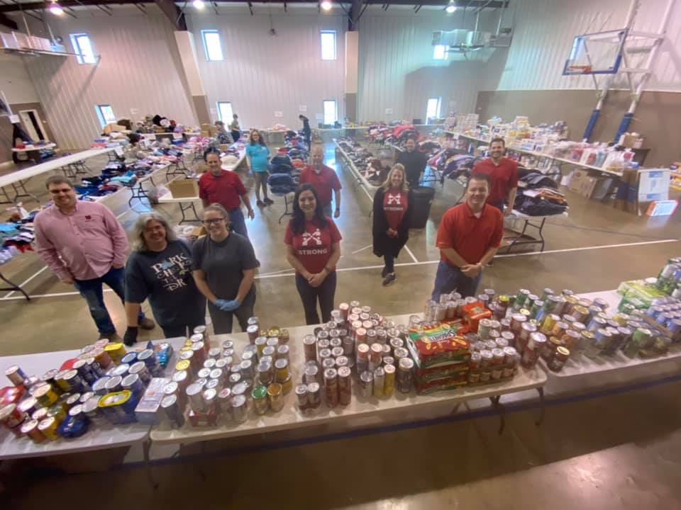 Volunteers standing amongst all the food, clothes and supplies at the donation center